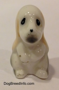 A white with tan and black bone china Basset Hound puppy figurine. The figurine has a black dot for a nose and black circles for eyes.