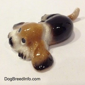 The front left side of a black and tan with white ceramic Basset Hound figurine that is laying down. The figurine is glossy.