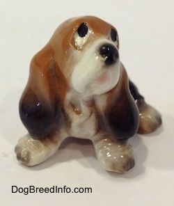 A black and brown with white ceramic Basset Hound figurine that is looking up. The figurines face lacks great detail.