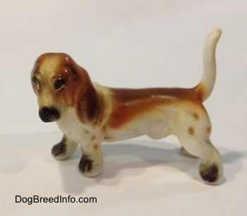 The left side of a brown and white porcelain Basset Hound figurine. The face of the figurine lacks fine detal.