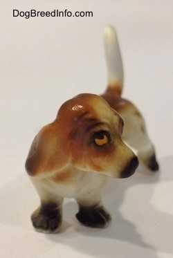 A brown and white porcelain Basset Hound figurine. The eyes of the figurine is detailed.