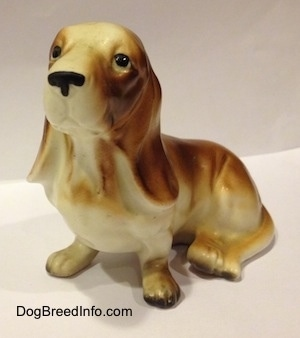 A brown and white porcelain Basset Hound figurine. The figurine is very detailed.