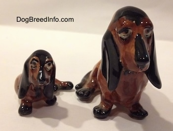 Two, a mother and a puppy, brown and black ceramic Basset Hounds figurines. The figurines lack eye details.