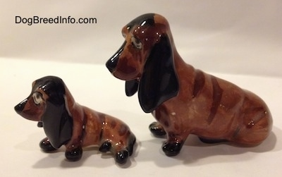 The left side of two, a mother and a puppy, brown and black ceramic Basset Hounds figurines. The figurines ears have fine details.