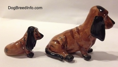 The right side of two, a mother and a puppy, brown and black ceramic Basset Hounds figurines. The figurines are glossy.