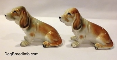 The left side of two brown and white with black ceramic Basset Hound figurines. The figurines have great ear details.