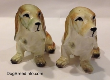 Two brown and white with black ceramic Basset Hound figurines. The figurines black circle eye details.
