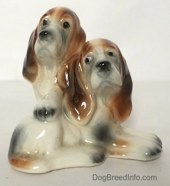 A ceramic Basset Hound figurine that is two Basset Hounds, one laying across a surface and the other standing up across its back.