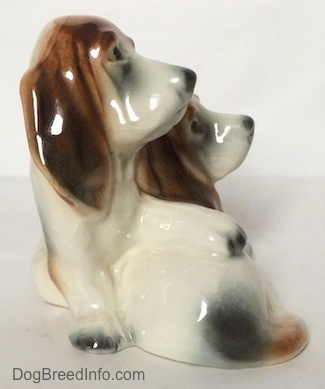 The right side of a ceramic Basset Hound figurine that is two Basset Hounds. The figurine is very glossy.