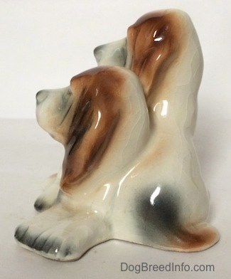 The left side of a ceramic Basset Hound figurine that is two Basset Hounds. The paws on a figurine are lacking detail.