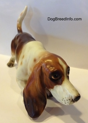 A brown and white porcelain Basset Hound figurine. The figurine has a very detailed face.