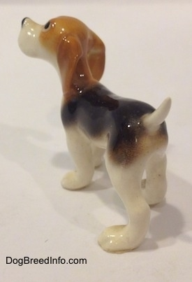 The back left side of a black and white with tan miniature Beagle figurine.