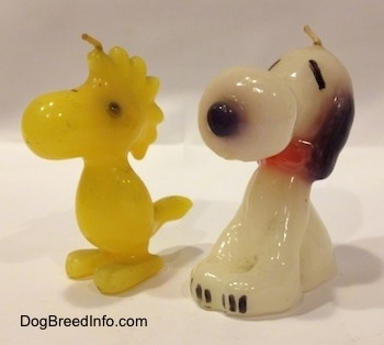 Close Up - Two candles side by side of Snoopy the Beagle sitting next to Woodstock the bird