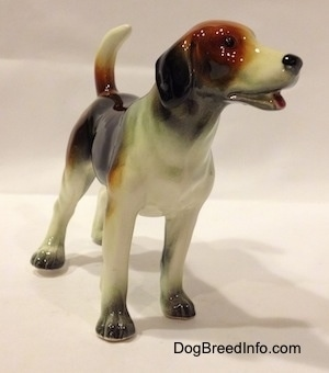 The front right side of a black, brown and white Beagle figurine. The eyes on the figurine is just a black circle.
