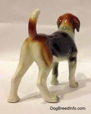 The back right side of a black, brown and white Beagle figurine. The painting on the figurine is great.