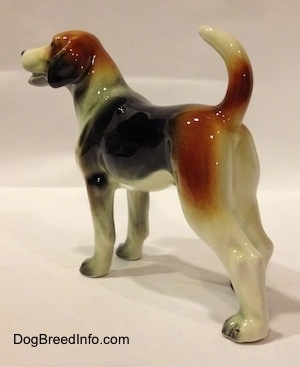 The back left side of a black, brown and white Beagle figurine. The ears of the figurine are detailed great. The dogs tail is high up in the air and the ears hang down low.