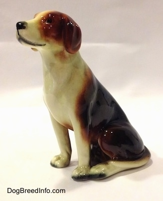The front left side of a black, brown and white porcelain Beagle figurine. The figurine has black dots for eyes.