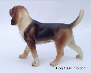 The left side of a black, brown and white porcelain Beagle Harrier figurine in a standing pose. The painting on the figurine is great.