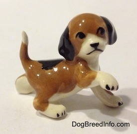 The right side of a brown, black and white miniature Beagle figurine in a standing pose with its paw up. The figurine is very glossy.