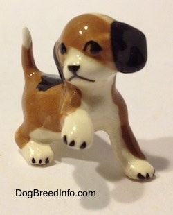 The front right side of a brown, black and white miniature Beagle figurine in a standing pose with its paw up. The figurine has a simple face.