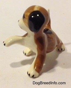 The front left side of a brown, black and white miniature Beagle figurine in a standing pose with its paw up. The figurine has no paw details.