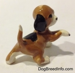 The back right side of a miniature Beagle figurine in a standing pose with its paw up.