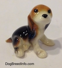 The right side of a black, brown and white Beagle puppy figurine. The figurine has no mouth.
