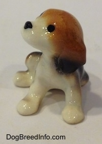 A black, brown and white Beagle puppy figurine. The figurine has circles for eyes.