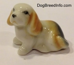 The left side of a bone china white with tan and black tiny Beagle puppy figurine. The figurine has a simple face.