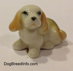 A bone china white with tan and black tiny Beagle puppy figurine. The figurine is very glossy.