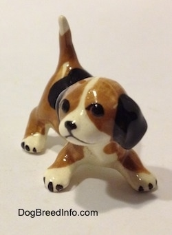 A brown, black and white miniature Beagle in a crouching pose. The figurine is very glossy.