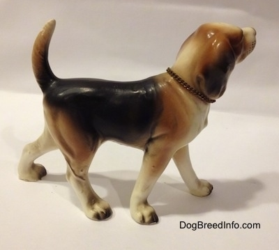 "The right side of a black, brown and white ceramic Beagle figurine with a chain ID collar that reads ""Beagle"". The figurine has very great leg details."