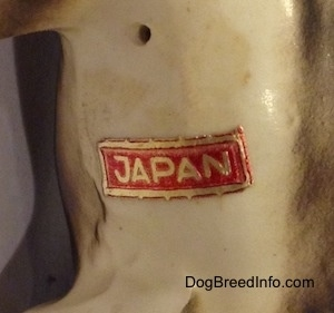 "Close up - The underside of a black, brown and white ceramic Beagle figurine with a chain ID collar that reads ""Beagle"". There is a sticker on the figurine and the sticker reads - JAPAN."