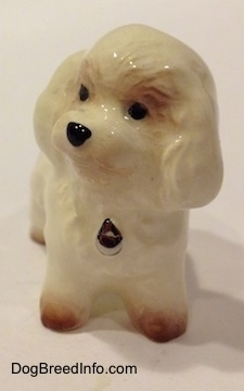 A white with tan miniature Bichon Frise dog figurine. The figurine has fine hair details. The dogs head has a round shape and the eyes are painted as black dots. There is a dog tag painted on the front. It has a black nose.