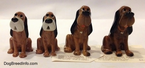 A line up of four Hagen-Renaker Bloodhound figurines. The figurines has very cartoon-y details with big black noses and black eyes.