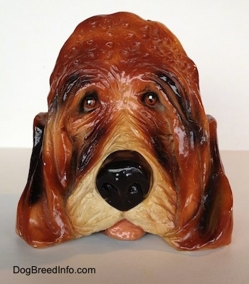 A highly detailed figurine of the head of a Bloodhound dog. The figurine has its tongue sticking out.