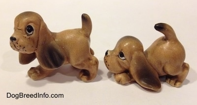 The left side of two Vintage miniature ceramic Bloodhound figurines. The ears of the figurines are easily visible against the body.
