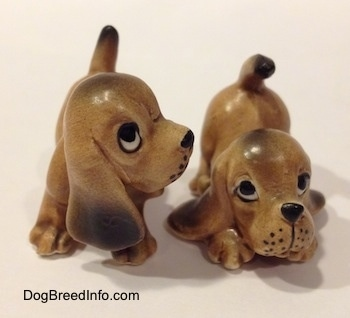 Two Vintage miniature ceramic Bloodhound figurines. The whiskers on the figurines face are dots.