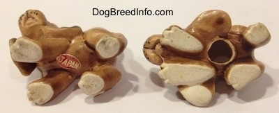 The underside of two Vintage miniature ceramic Bloodhound figurines. There is a sticker with the word -JAPAN - on the underside of the left most figurine and the one on the right has a hole on its underside.