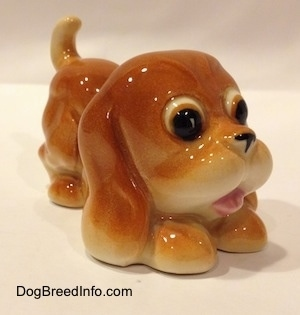 The front right side of a tan Cartoon style Bloodhound puppy figurine. The figurine is in a play bow pose.