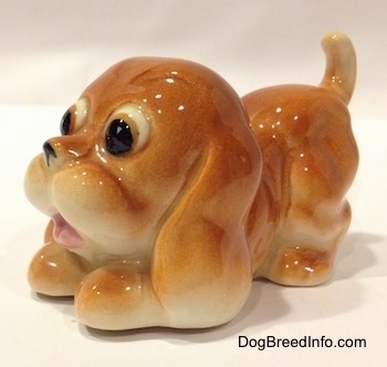 The front left side of a tan Cartoon style Bloodhound puppy figurine. The eyes of the figurine are big boldging eyes.