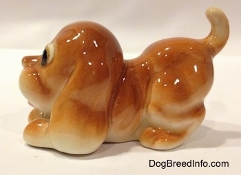 The left side of a tan Cartoon style Bloodhound puppy. The figurine has its mouth open and a tongue sticking out.