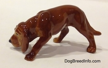 The left side of a Hagen-Renaker miniature red variation of a Bloodhound figurine. The figurine has great paw details.
