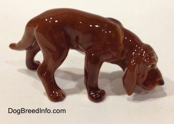 The right side of a Hagen-Renaker miniature red variation of a Bloodhound figurine. The figurine is very glossy. The dog has its nose to the ground.
