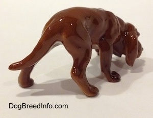 The back right side of a Hagen-Renaker miniature red variation of a Bloodhound figurine. The figurine is very detailed.