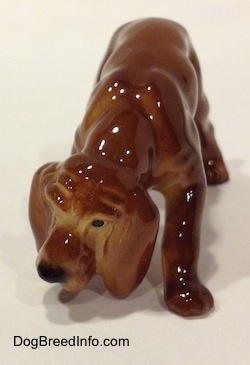 A Hagen-Renaker miniature red variation of a Bloodhound figurine. The figurine has great wrinkles on the face details.