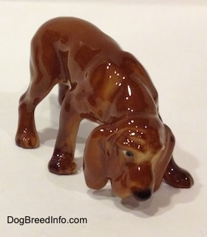 The front right side of a Hagen-Renaker miniature red variation of a Bloodhound figurine. The figurine has great eye details with black and white paint.