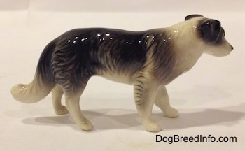 The right side of a Retired Hagen-Renaker black with white Border Collie style 1 figurine. It is hard to differentiate the ears from the head.