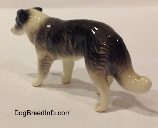 The back left side of a Retired Hagen-Renaker black with white Border Collie style 1 figurine. The paws of the figurine are not very detailed.