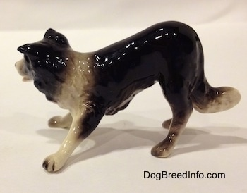 The left side of a Hagen-Renaker miniature black with white Border Collie figurine. The figurine is glossy.